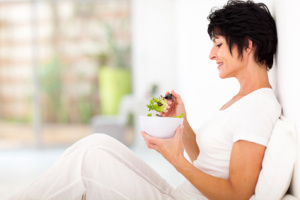 elegant middle aged woman eating salad